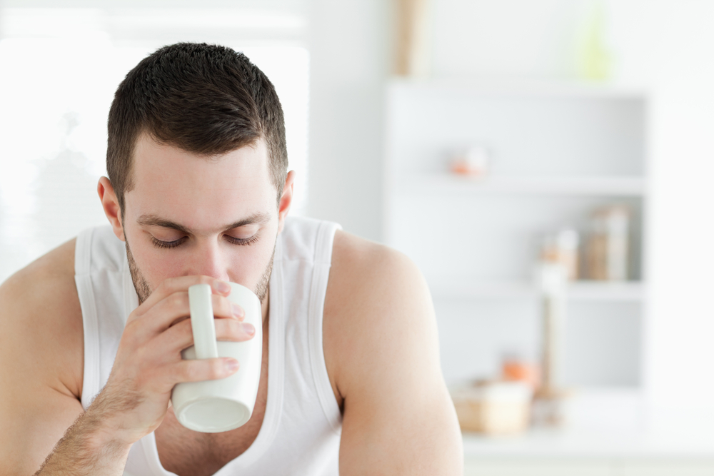 Close up of a man having coffee in his kitchen