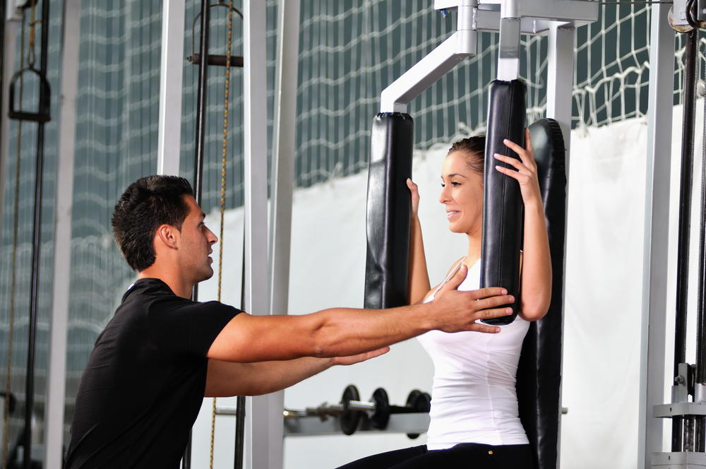 woman in the fitness gim working out with personal trainer coach-1